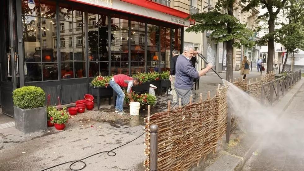 Nhân viên quán cà phê ở Paris dọn dẹp hôm 17/5, hai ngày trước khi các nhà hàng và quán bar ở Pháp được phép mở cửa lại. Ảnh: AFP