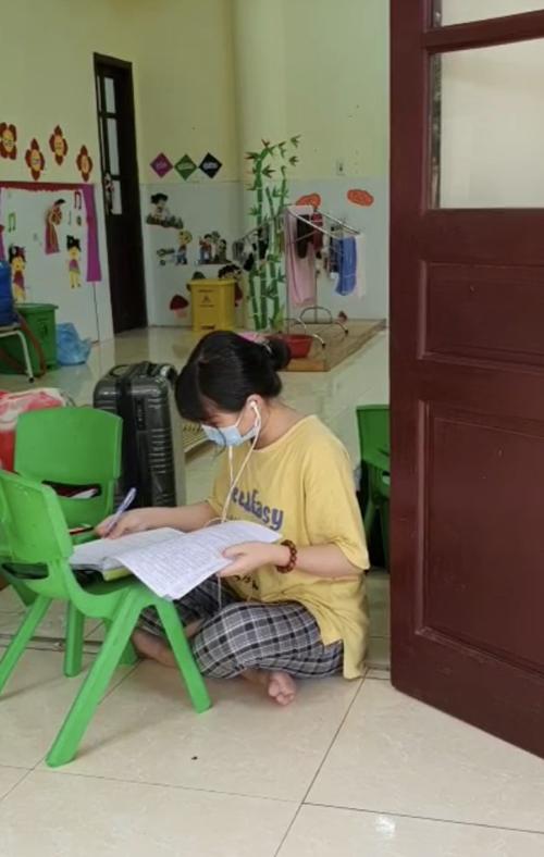 Mạng kém nên nhiều học sinh trong khu cách ly phải kê ghế ngồi ra ngoài cửa hứng sóng wifi để học bài. Ảnh: NVCC.