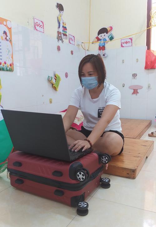 Chị Quý dùng valy làm bàn đặt máy tính lên để làm việc trong khu cách ly. Ảnh: NVCC.