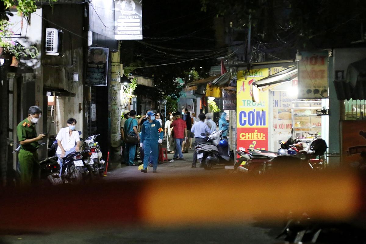 Nhân viên y tế đang lấy mẫu ở các hộ dân sống gần ca nghi nhiễm, tối 20/5. Ảnh: Đình Văn.