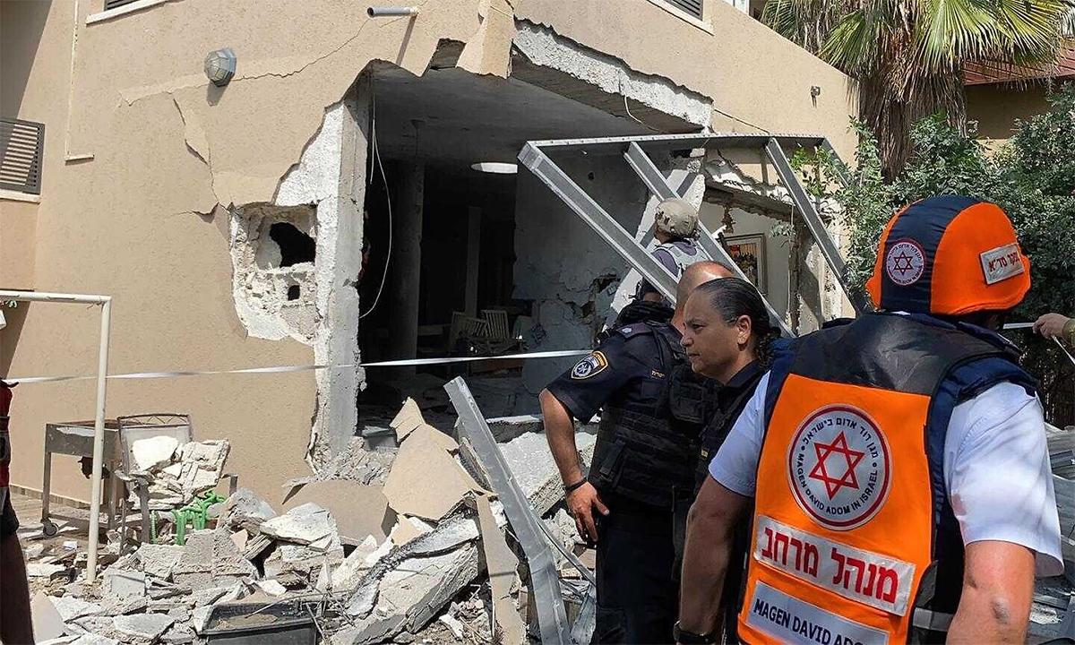Cảnh sát và nhân viên cứu hộ Israel bên cạnh một ngôi nhà ở thành phố Ashkelon bị trúng rocket của Hamas ngày 20/5. Ảnh: Magen David Adom.