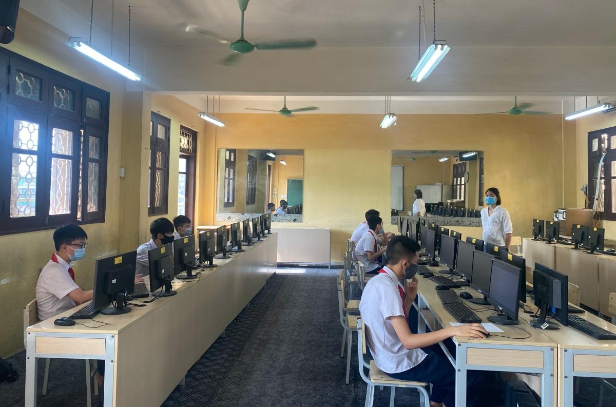 Một số học sinh không đảm bảo thiết bị nên đến trường để làm bài kiểm tra trực tuyến. Các em được bố trí ngồi giãn cách, đeo khẩu trang trong lúc làm bài. Ảnh: Nhà trường cung cấp