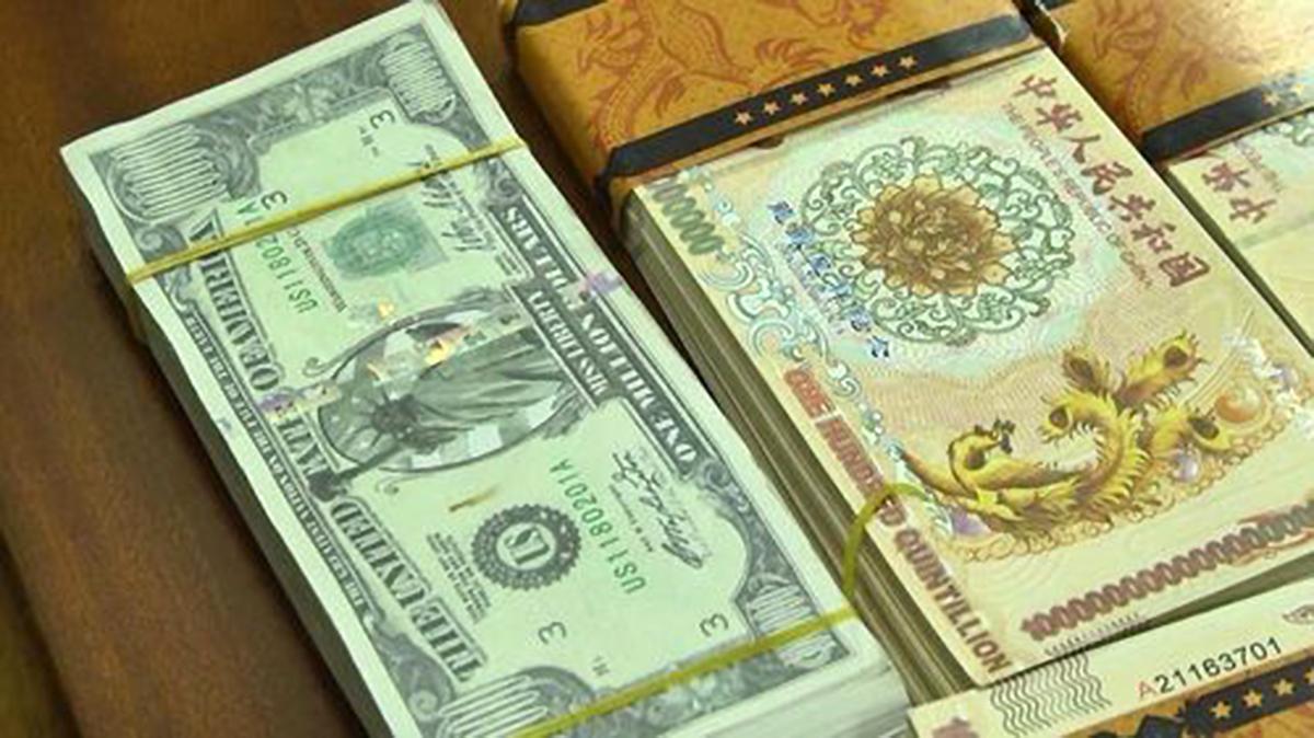 Tiền cổ giả (phải) và xấp tiền mệnh giá một triệu USD nhóm lừa đảo nói tìm thấy trong kho báu quốc gia. Ảnh: Nhật Vy.