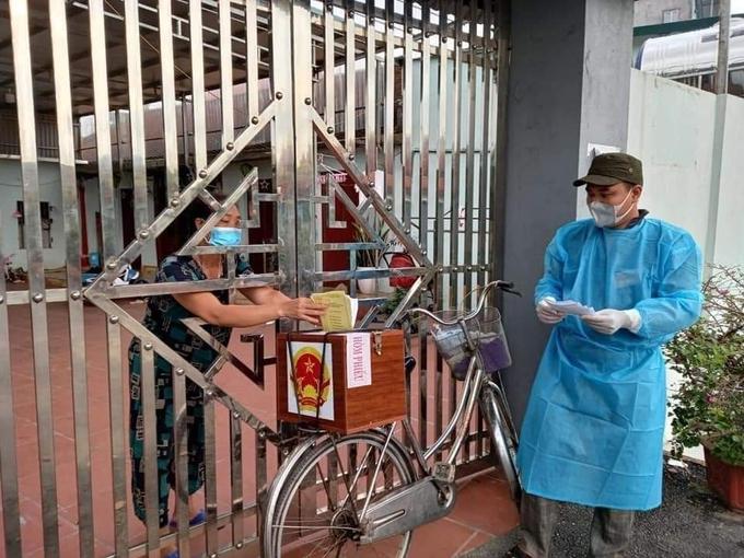 Lực lượng chức năng thôn Chùa, xã Tăng Tiến, huyện Việt Yên, tỉnh Bắc Giang dùng xe đạp chở hòm phiếu đến từng nhà để cử tri bỏ phiếu. Ảnh: Hữu Trình