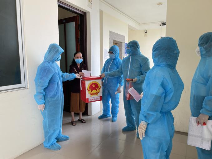 Lực lượng chức năng mang hòm phiếu đến khu cách ly tập trung tại trường Cao đẳng thống kê Bắc Ninh để cử tri bỏ phiếu. Bắc Ninh là địa phương có số ca nhiễm cao thứ hai cả nước với 448 ca Covid-19. Ảnh: Gia Chính
