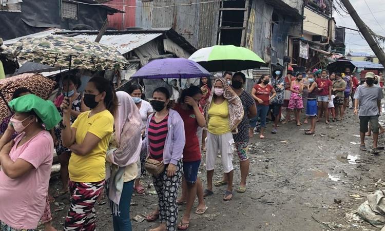 Người dân xếp hàng chờ nhận thực phẩm tại một bếp ăn cộng đồng ở thủ đô Manila, Philippines. Ảnh: CNN.