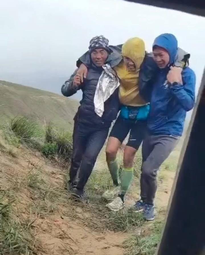 Chu Khả Minh (trái) cùng một vận động viên việt dã, dìu người đuối sức vào hang trú ẩn hôm 22/5. Ảnh: The Paper