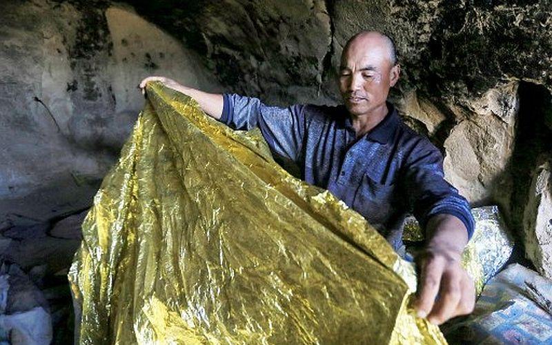 Chu Khả Minh khoe tấm giữ nhiệt trong hang trú ẩn hôm 24/5. Ảnh: AFP