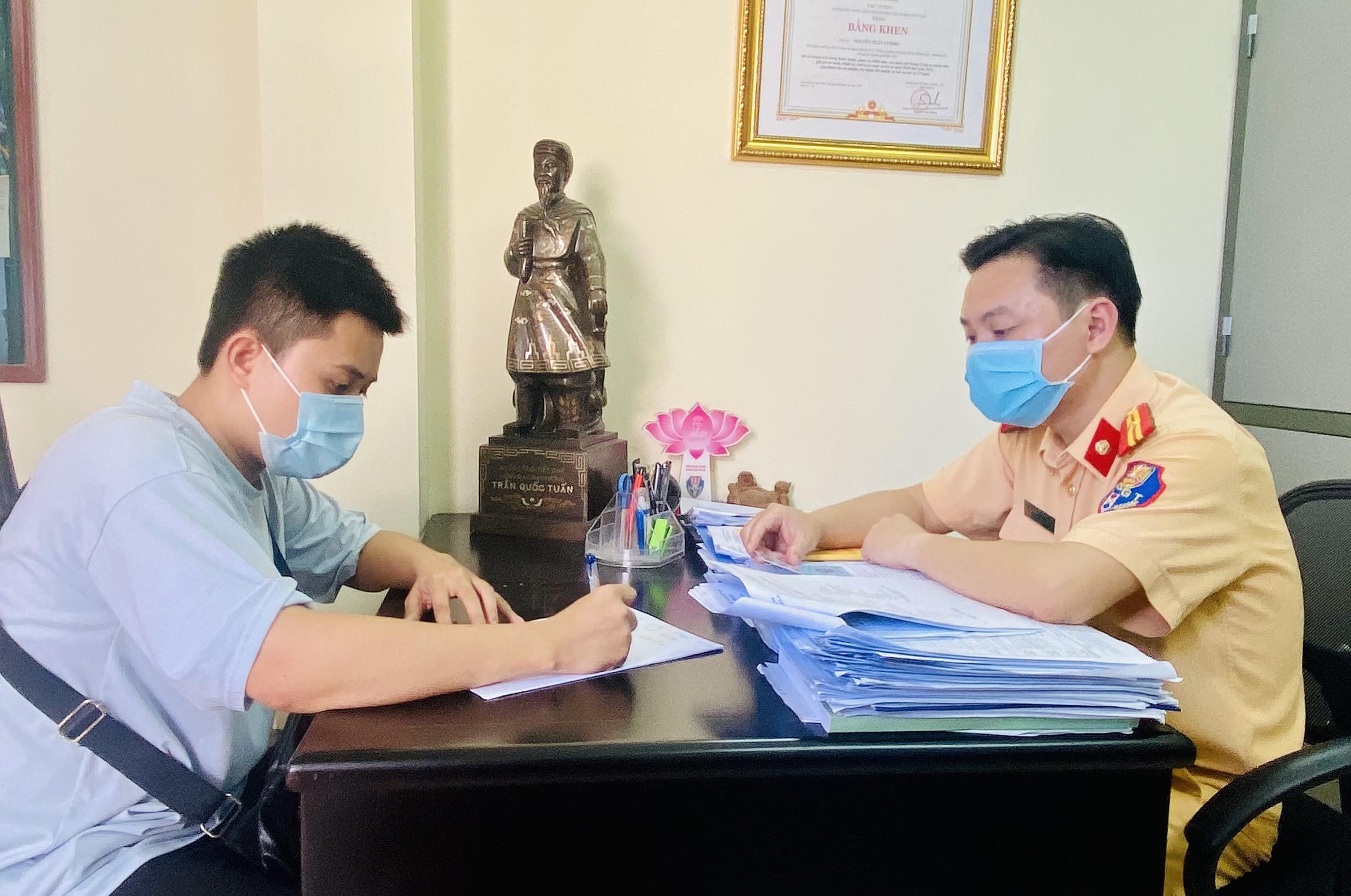 Thiếu tá Nguyễn Tuấn Cường (phải) hướng dẫn Sơn hoàn thiện các thủ tục để nhận lại chiếc xe. Ảnh: NVCC