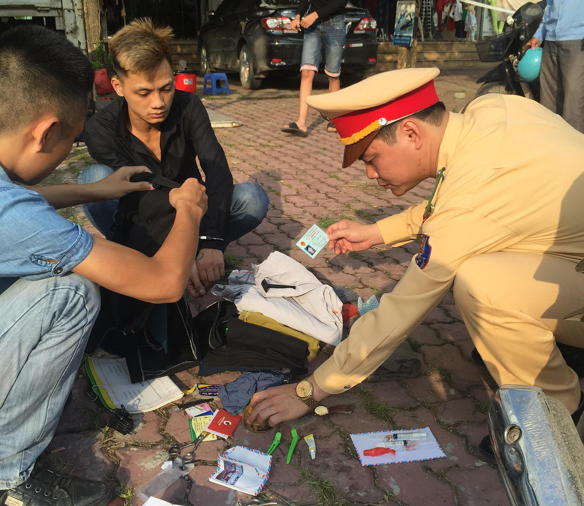 Thiếu tá Nguyễn Tuấn Cường (phải) kiểm tra hành chính hai nam thanh niên khả nghi, phát hiện nhiều ống tiêm và chất nghi la ma tuý. Ảnh: NVCC