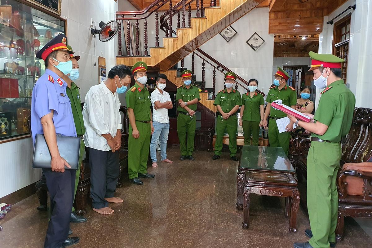 Công an đọc lệnh bắt giữ Nguyễn Quyền cùng hai con trai. Ảnh: Hồng Nhung