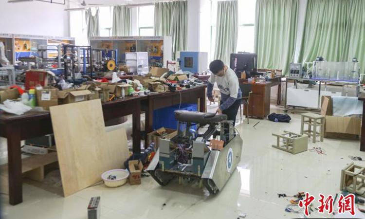 Xe lăn leo cầu thang thông minh do sinh viên bại não Liu Xin (23 tuổi) sáng chế. Ảnh: CNS.