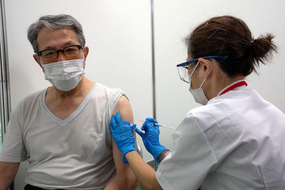 Một người dân Nhật Bản tiêm vaccine Covid-19 của Moderna tại trung tâm tiêm chủng mới mở ở Tokyo hôm 24/5. Ảnh: Reuters.