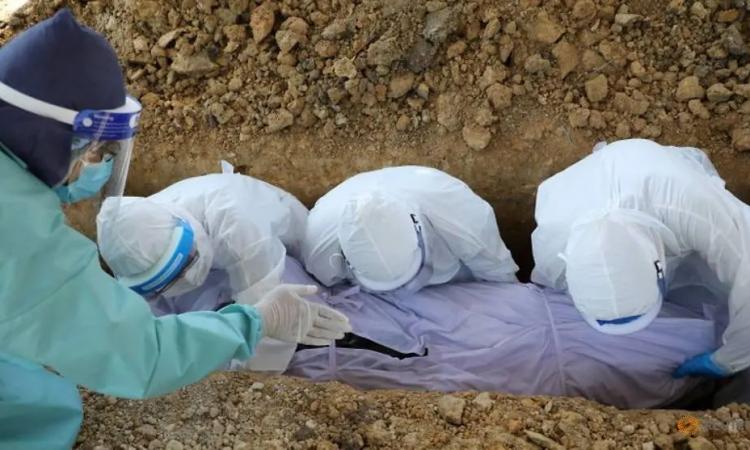 Nhóm tình nguyện đào một cho một bệnh nhân Covid-19 ở nghĩa trang tại Gombak, Malaysia, hôm 23/5. Ảnh: Reuters.