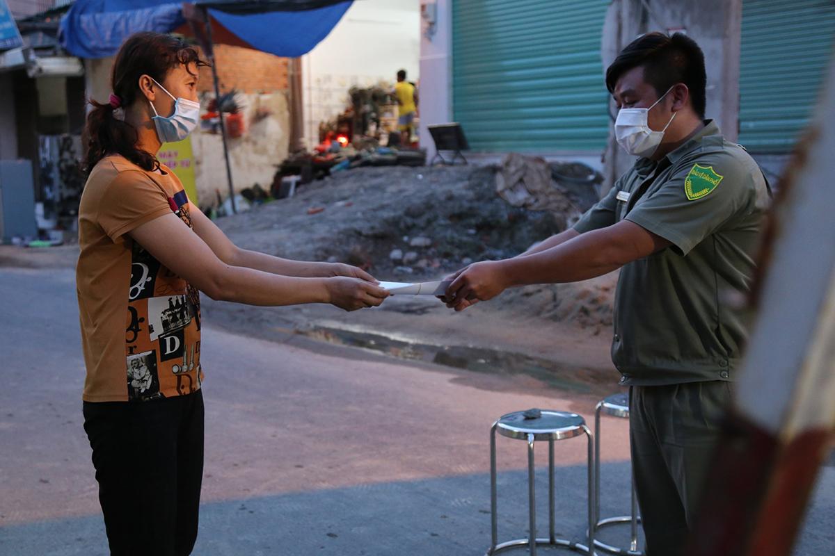 Người dân (trái) phường Thạnh Lộc, quận 12, được phát phiếu hỗ trợ mua đồ dùng, chiều 30/5. Ảnh: Đình Văn.