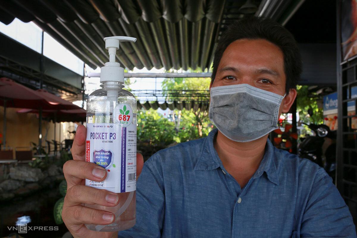 Anh Đức với nước sát khuẩn do mình sản xuất. Ảnh: Nguyễn Đông.