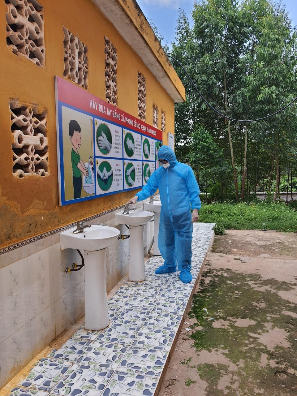 Hàng sáng, thầy Thành mặc đồ bảo hộ, đi kiểm tra đường điện, nước, các thiết bị quanh trường để chắc chắn cơ sở vật chất đảm bảo cho các em cách ly. Ảnh: NVCC.
