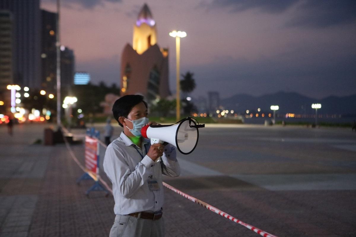 Anh Lê Thanh Trung, cán bộ phường ở Nha Trang chốt trực tại Quảng Trường 2 Tháng 4, phát loa nhắc nhở người dân đeo khẩu trang, không tập trung đông người, tối 31/5. Ảnh: Xuân Ngọc.