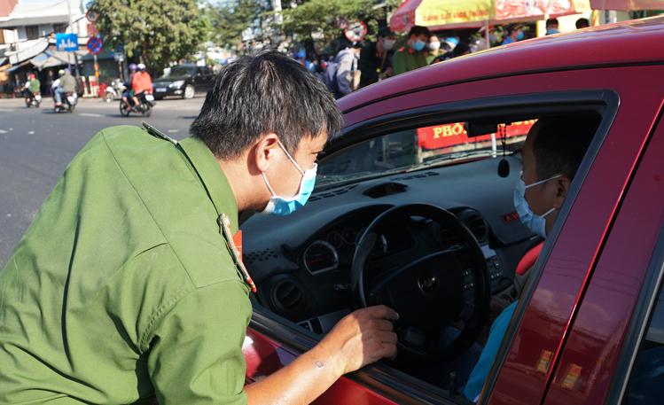 Công a kiểm tra ôtô vào thành phố, nhắc nhở người dân đeo khẩu trang tại cầu Vĩnh Bình (cửa ngõ TP HCM - Bình Dương). Ảnh: Mạnh Tùng.