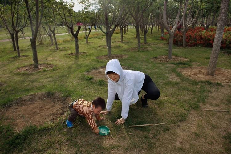 Zhang A Lan chơi đùa với con trai trong một công viên gần nơi cô sinh sống ở tỉnh Hà Bắc. Ảnh: NYTimes.
