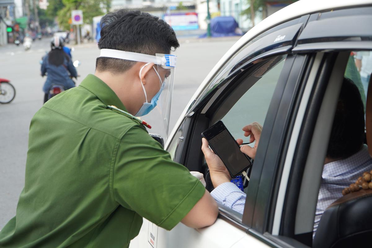 Công an kiểm tra khai báo y tế online với người vào quận Gò Vấp, sáng 2/6. Ảnh: Gia Minh.