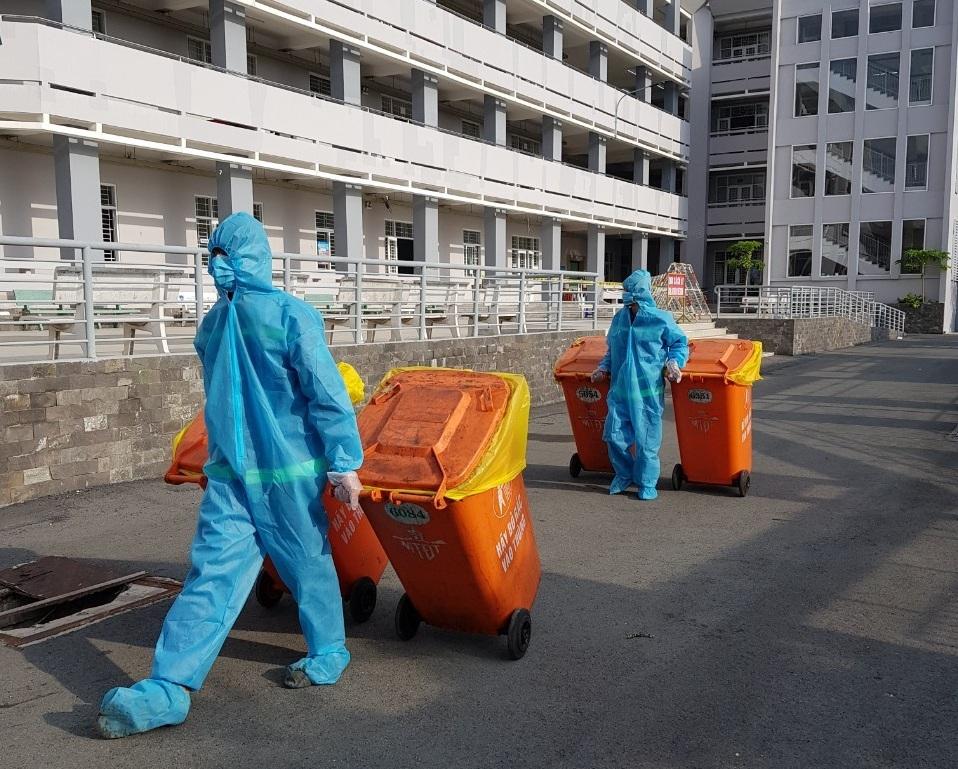 Nhân viên công ty Môi trường Đô thị TP HCM thu gom rác thải tại một khu cách ly tập trung. Ảnh: Lan Thương.