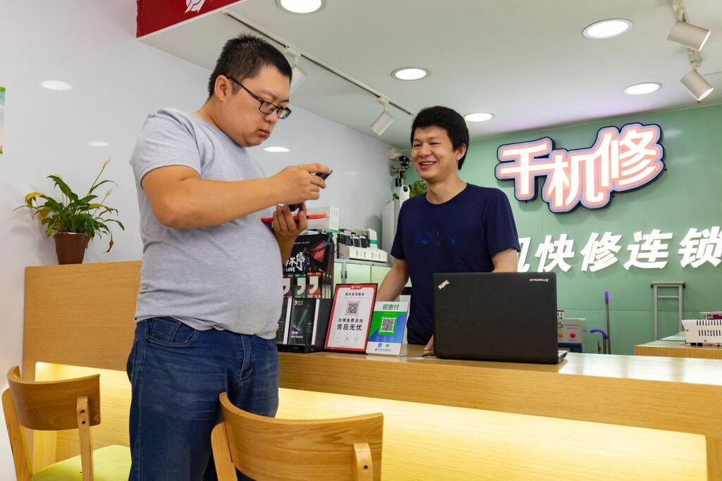 Hoàng Ngọc Long trao đổi với khách hàng ở Quảng Châu. Ảnh: NYTimes.