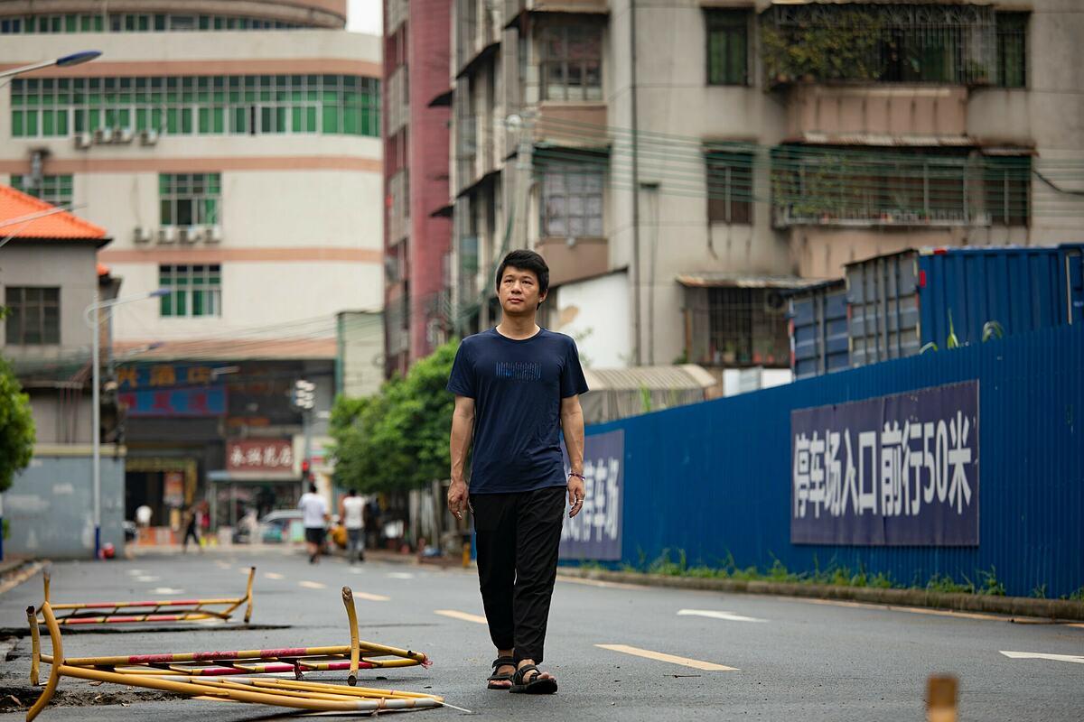 Hoàng Ngọc Long, thợ sửa điện thoại ở Trung Quốc. Ảnh: NYTimes.
