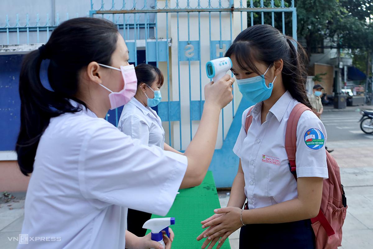 Thí sinh đo thân nhiệt trước khi vào phòng thi tuyển lớp 10 tại TP Nha Trang, sáng 3/6. Ảnh: Xuân Ngọc.