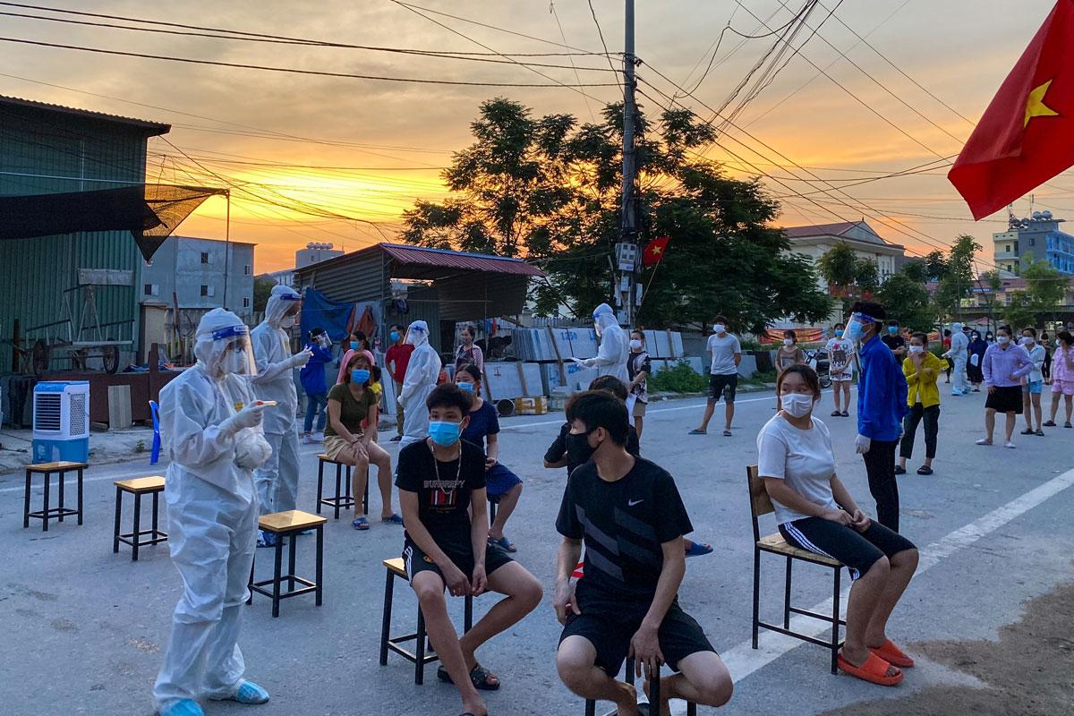 Tình nguyện viên Học viện Y dược học cổ truyền lấy mẫu xét nghiệm người dân My Điền (Việt Yên, Bắc Giang) vào lúc chiều muộn để tránh nắng nóng 40 độ C. Ảnh: Hồng Nhung