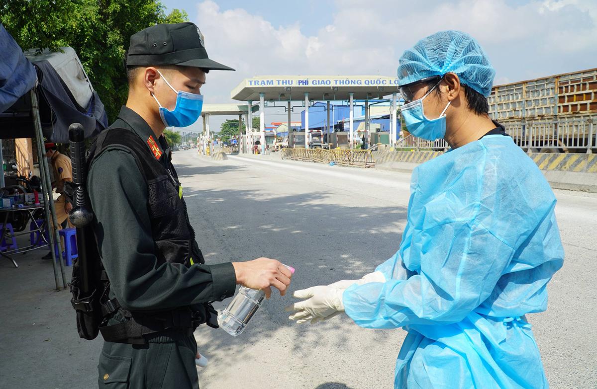 Một tài xế chở hàng từ TP HCM được đo thân nhiệt, rửa tay sát khuẩn khi vào tỉnh Đồng Nai, sáng 5/6. Ảnh: Phước Tuấn.