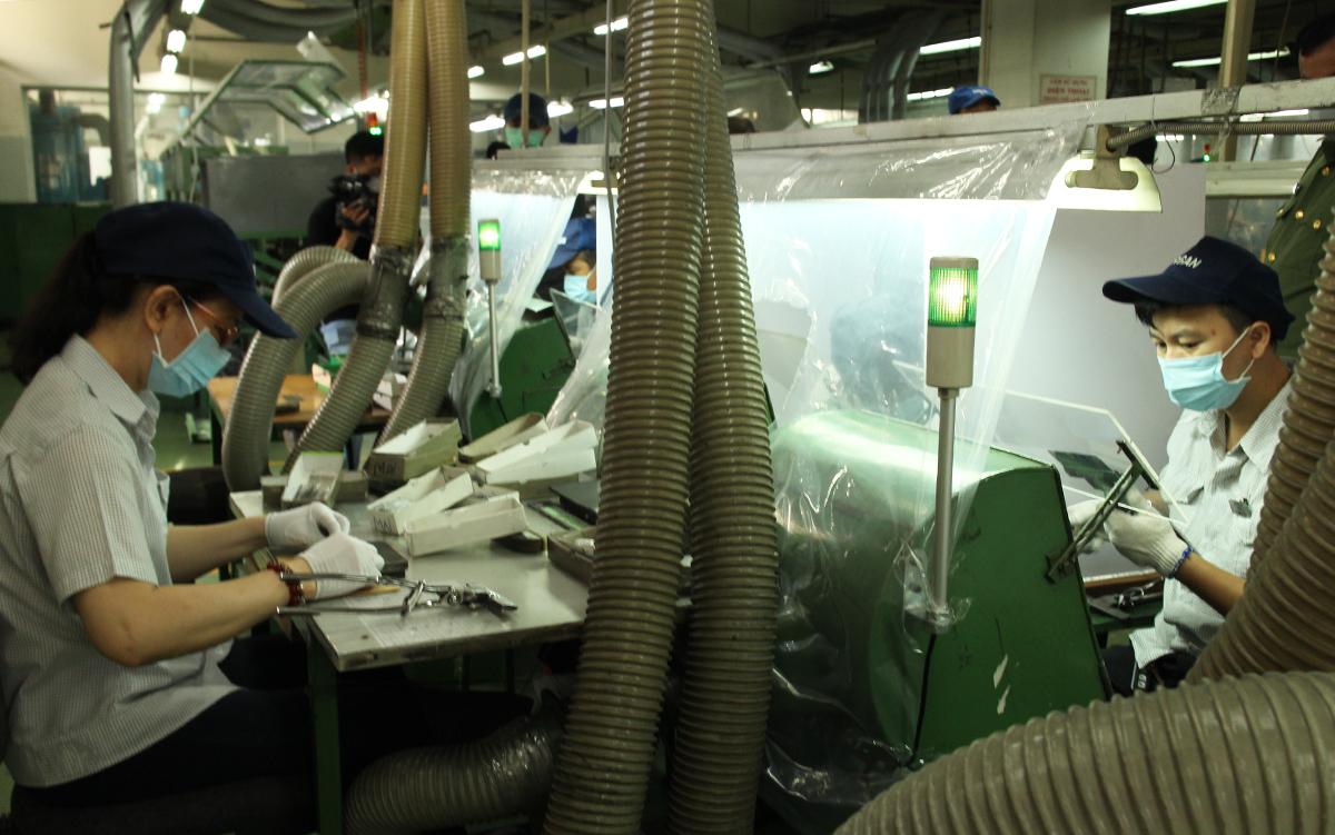 Một nhà máy tại Khu chế xuất Tân Thuận, quận 7, lắp màn chắn ở những chuyền công nhân ngồi đối diện để phòng dịch. Ảnh: An Phương.