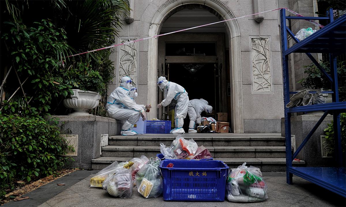 Nhân viên quản lý nhà ở mặc đồ bảo hộ phân phối lương thực cho một khu dân cư bị phong tỏa tại thành phố Quảng Châu, Trung Quốc ngày 2/6. Ảnh: Reuters.