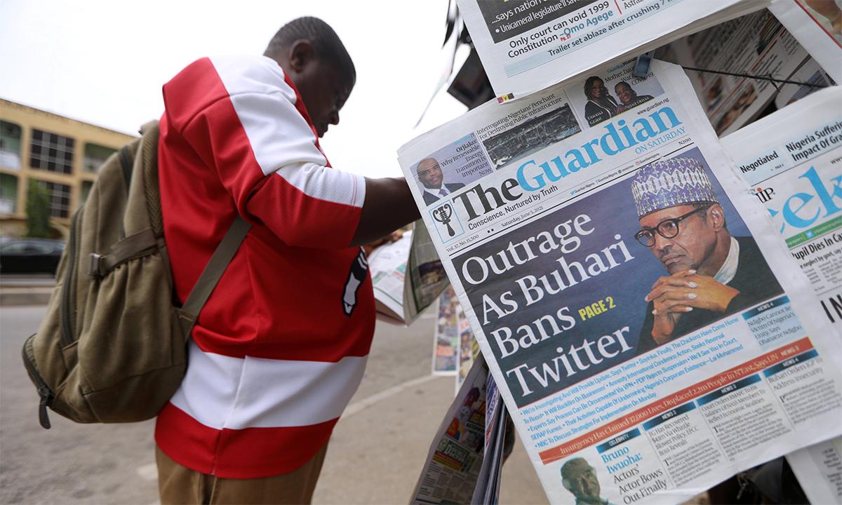 Một người Nigeria đọc một tờ báo đưa tin về lệnh cấm Twitter trước sạp báo tại thủ đô Abuja ngày 5/6. Ảnh: Reuters.