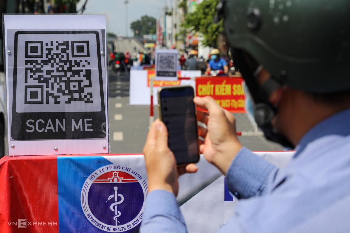 Người dân quét mã QR Code khai báo y tế điện tử khi đi qua chốt kiểm soát dịch bệnh tại quận Gò Vấp, TP HCM. Ảnh: Quỳnh Trần