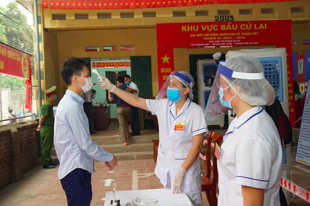 Lực lượng y tế kiểm tra thân nhiệt một cử tri tại điểm bỏ phiếu ở xã Tráng Việt, Mê Linh. Ảnh: Phạm Hùng.