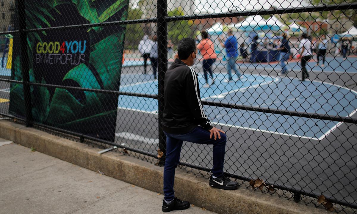 Người đàn ông đứng bên ngoài nhìn vào một địa điểm tiêm chủng ở quận Bronx, thành phố New York. Ảnh: Reuters.