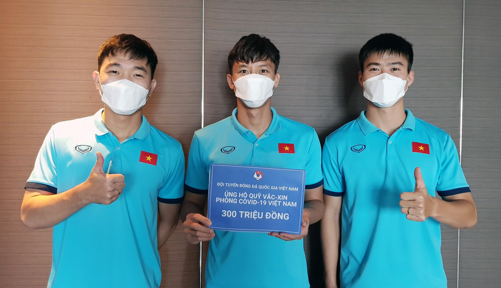 Thủ quân Quế Ngọc Hải (giữa) cùng các đồng đội ủng hộ Quỹ vaccine phòng Covid-19. Ảnh: VFF.