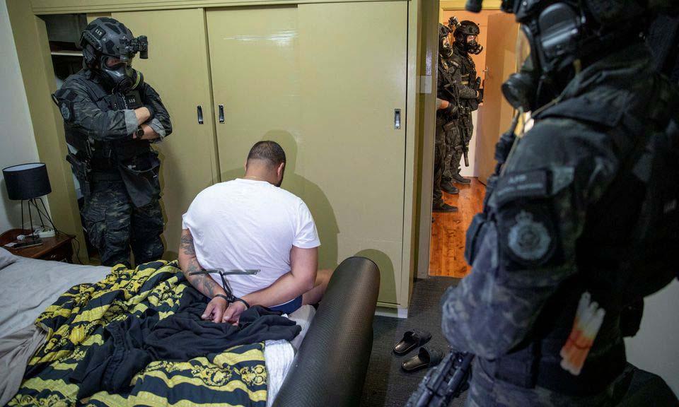 Một nghi phạm bị Cảnh sát Liên bang Australia bắt sau chiến dịch truy quét tội phạm băng đảng toàn cầu hợp tác với FBI. Ảnh: Reuters.
