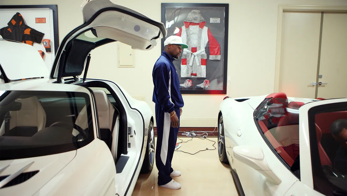 Boxer stands next to sports cars in his private garage in Las Vegas.  Photo: USA Today