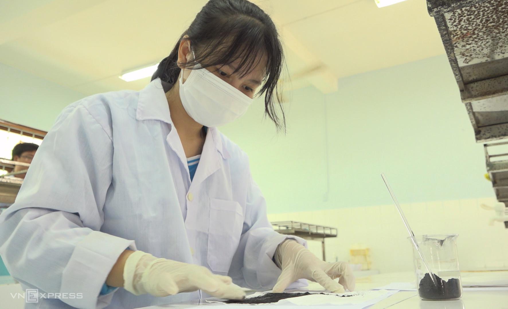 Than hoạt tính được trải đều trên lớp giấy kháng khuẩn, phần quan trọng của khẩu trang. Ảnh: Phúc Hiền. Ảnh: Phúc Điền