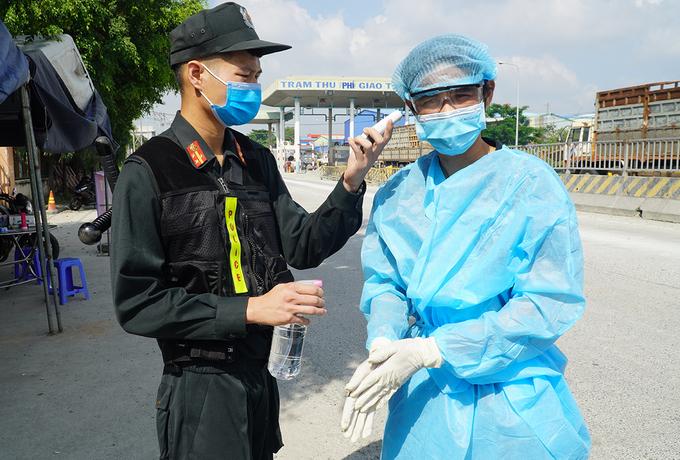 Một tài xế chở hàng từ TP HCM được đo thân nhiệt, rửa tay sát khuẩn khi vào tỉnh Đồng Nai sáng 5/6. Ảnh: Phước Tuấn