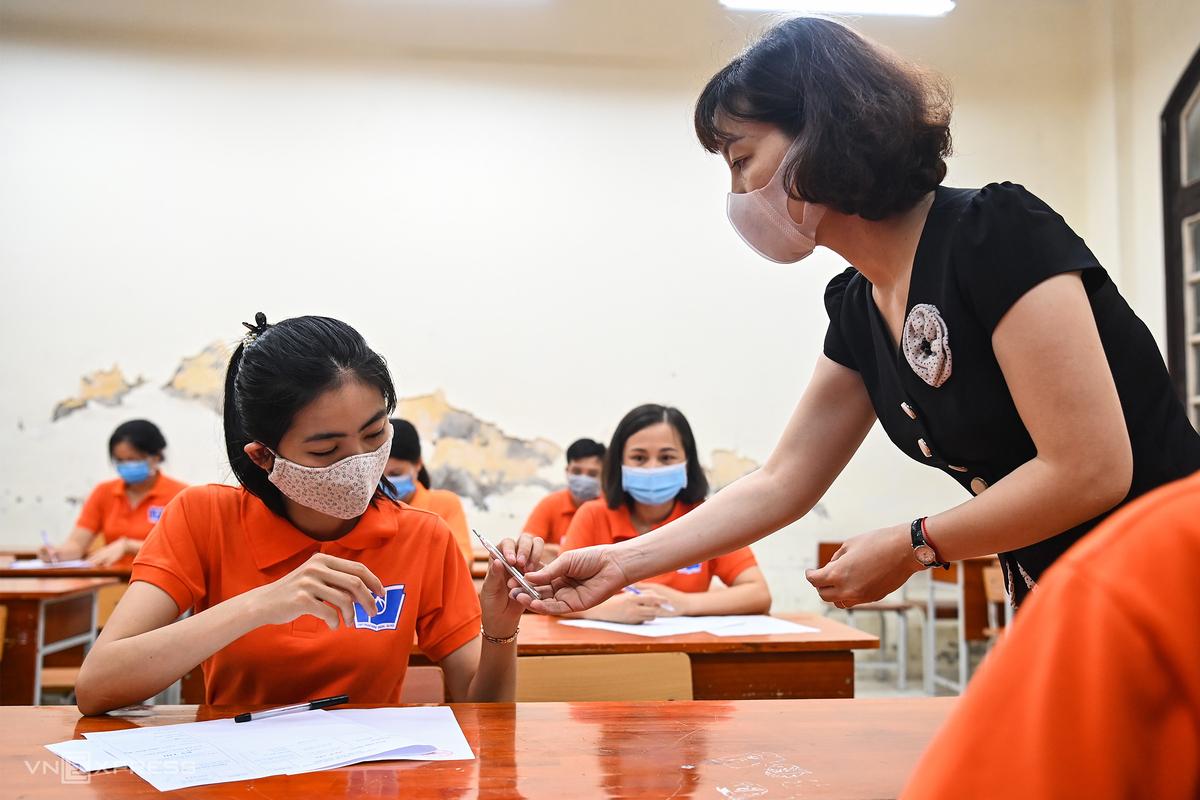Giáo viên và nhân viên y tế diễn tập tình huống lấy mẫu xét nghiệm tại phòng cách ly tạm thời với thí sinh có biểu hiện không khỏe trong lúc làm bài, sáng 8/6. Ảnh: Giang Huy