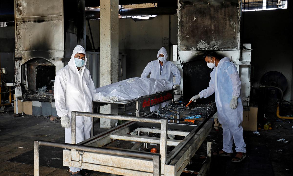 Tình nguyện viên chuẩn bị hỏa tảng thi thể một người chết vì Covid-19 tại Surat, Ấn Độ ngày 11/5. Ảnh: Reuters.