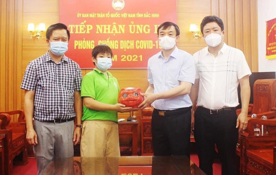 Đỗ Quốc Hưng trao chú lợn tiết kiệm đã nuôi ba năm cho đại diện Uỷ ban Mặt trận Tổ Quốc Việt Nam tỉnh Bắc Ninh. Ảnh: Gia đình cung cấp.