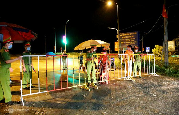 Lực lượng chức năng lập chốt kiểm soát tại khu vực liên quan ba ca nghi nhiễm ở thị trấn Lộc Hà, tối 11/6. Ảnh: Hùng Lê
