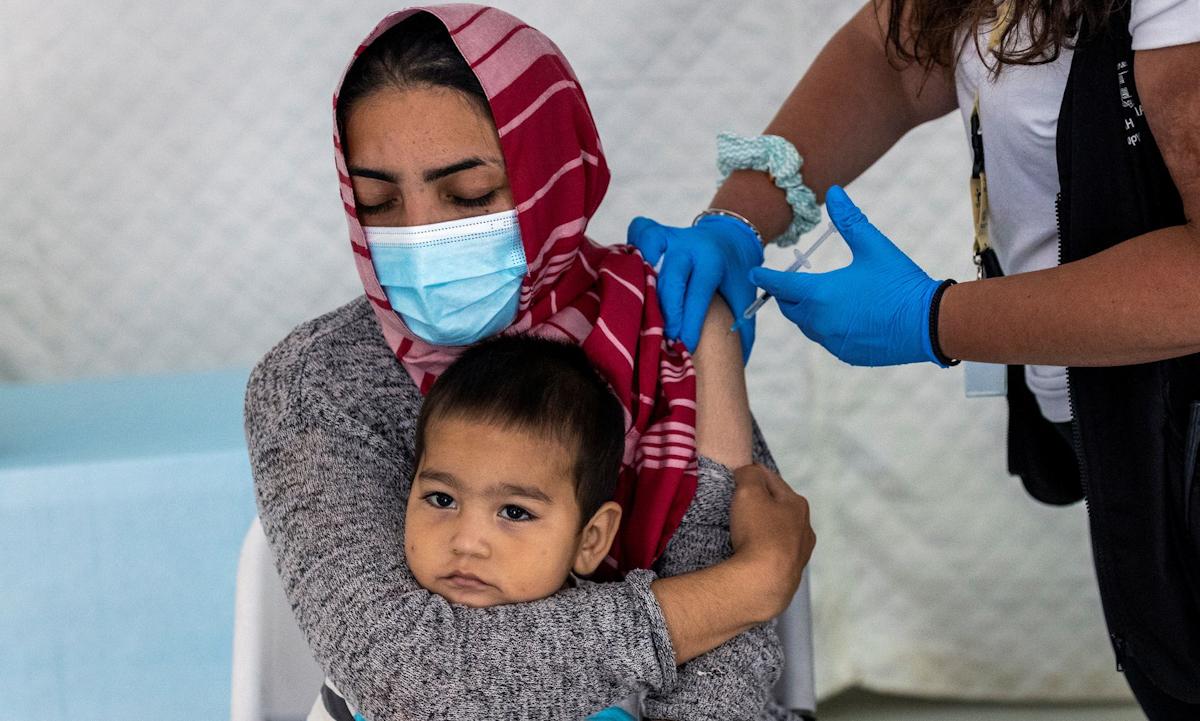 Một phụ nữ nhập cư ôm đứa con nhỏ khi được nhân viên y tế tiêm vaccine Covid-19 tại đảo Lesbos, Hy Lạp hôm 3/6. Ảnh: Reuters.