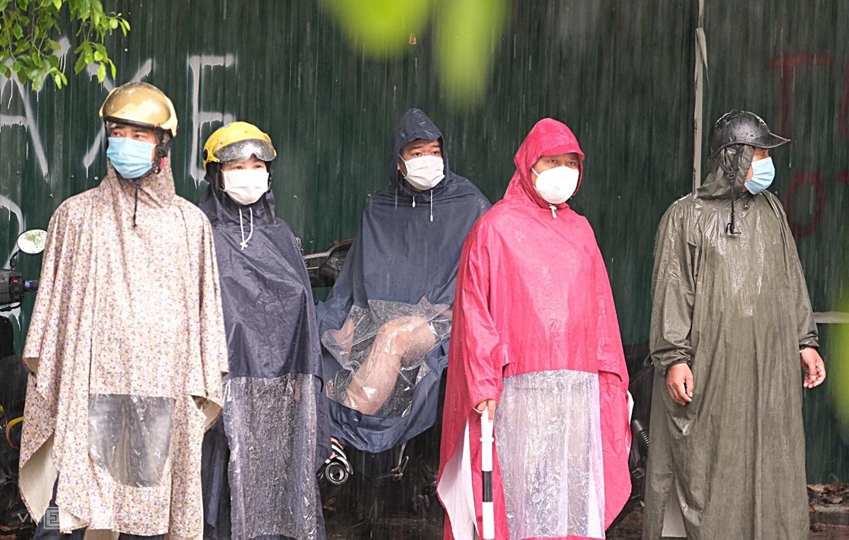 Nhiều phụ huynh vẫn mặc nguyên áo mưa, đội mũ bảo hiểm đứng đợi con dưới mái hiên gần điểm thi trường THCS Nam Trung Yên, quận Cầu Giấy, sáng 13/6. Ảnh: Dương Tâm