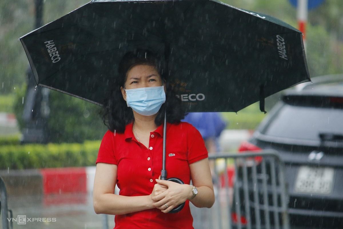 Một phụ huynh nán lại ở cổng trường THCS Yên Hòa đợi con, sáng 13/6. Ảnh: Thanh Hằng