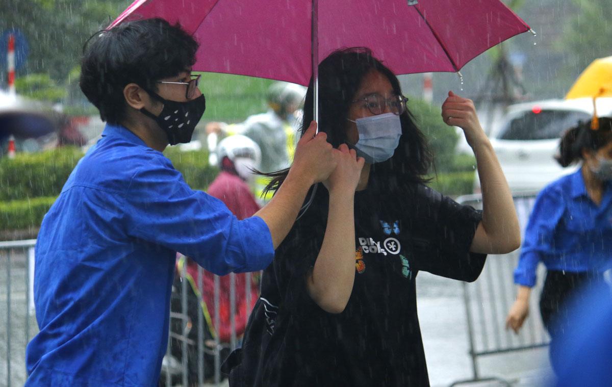 Thanh niên tình nguyện che ô cho thí sinh đi từ cổng trường vào khu vực thi. Ảnh: Thanh Hằng.